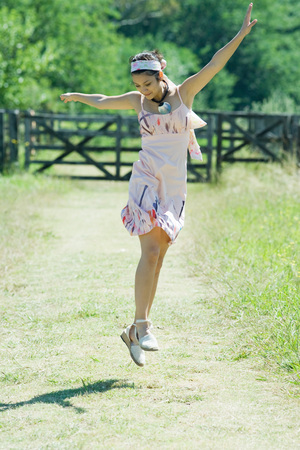 scarves: Young woman jumping in rural setting