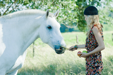 Young woman feeding horse, holding hay and apples