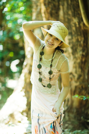 Young woman standing in woods, holding sunhat on head, smiling at camera