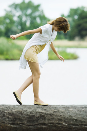 Young woman walking across log with arms out, looking down LANG_EVOIMAGES