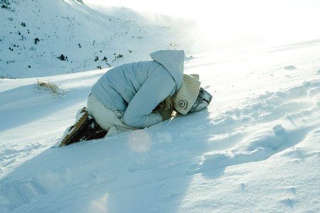 Teen girl curled up on snow LANG_EVOIMAGES