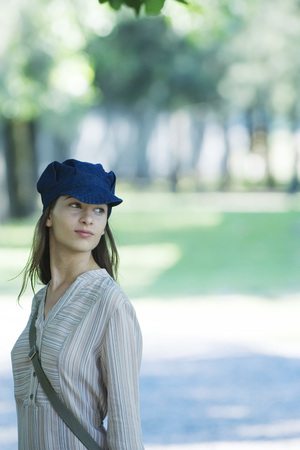 Young woman in park, wearing cap, waist up
