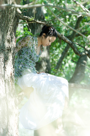 Young woman sitting in tree with eyes closed LANG_EVOIMAGES
