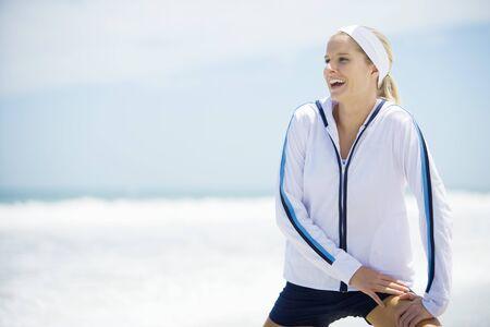 Junge Frau in der aktiven Abnutzung auf dem Strand, dehnt aus und lacht LANG_EVOIMAGES