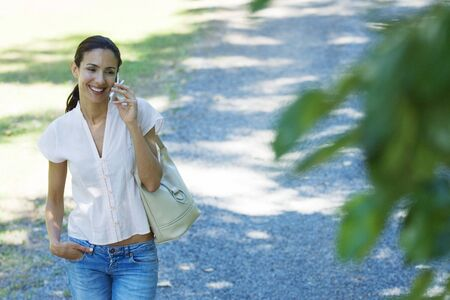 Casually dressed woman using cell phone, smiling as she walks through park, purse on shoulder LANG_EVOIMAGES
