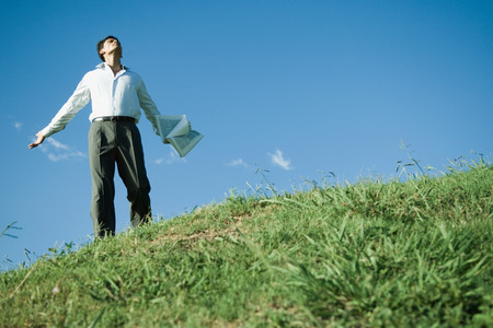 Businessman standing on grassy hill, arms out, head back and eyes closed, low angle view LANG_EVOIMAGES
