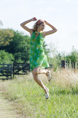 beauties: Young woman in sundress jumping in rural field LANG_EVOIMAGES