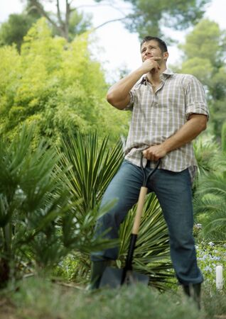 Man doing yard work, holding shovel, looking up LANG_EVOIMAGES