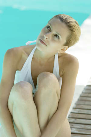 Young woman sitting by edge of pool