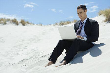 Businessman sitting on sand dune, using laptop
