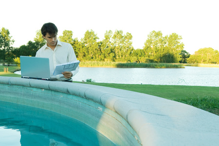 Man leaning on edge of pool, studying blueprints and using laptop