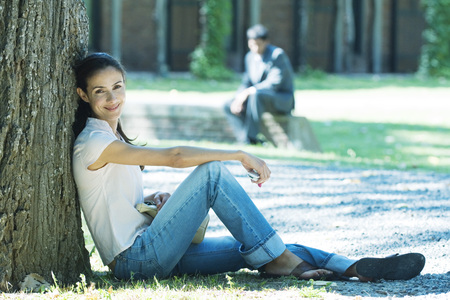 Woman sitting on ground, leaning against tree, smiling at camera