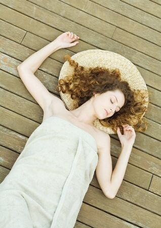 Woman lying on deck, wrapped in towel, head on mat
