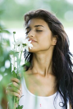 Young woman smelling flowers with eyes closed, close-up LANG_EVOIMAGES