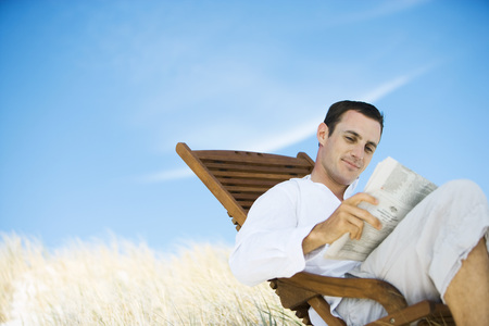 Young man sitting in deck chair, reading newspaper