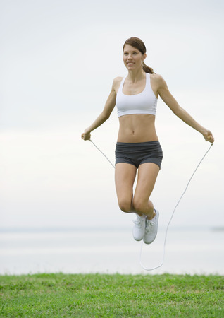Young woman jumping rope by lakeside LANG_EVOIMAGES