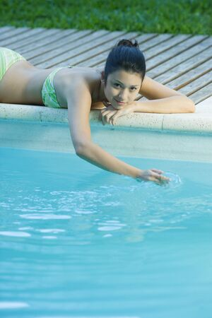 Woman lying by pool, touching surface of water LANG_EVOIMAGES