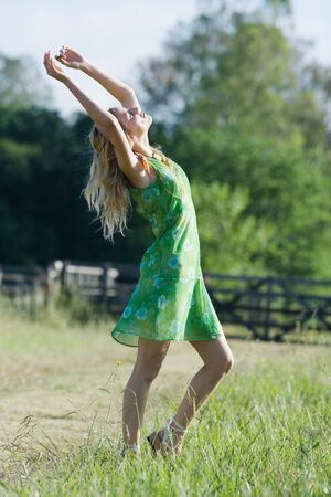 Young woman in sundress standing in rural field with arms raised