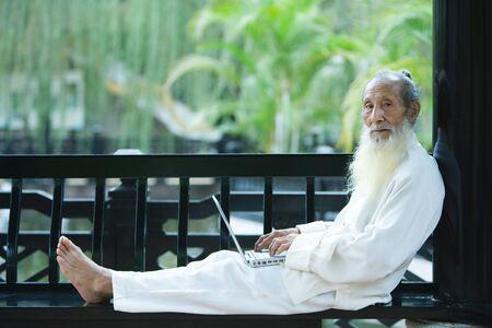 Elderly man wearing traditional Chinese clothing, using laptop, full length