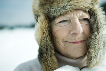 furs: Senior woman standing in snowy landscape, head and shoulders