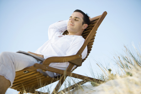 Young man sitting in deck chair, smiling, low angle view LANG_EVOIMAGES