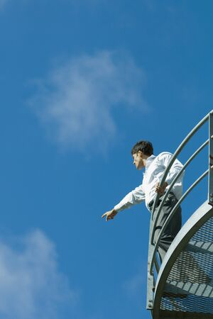 Businessman standing on metal balcony, pointing to distance, low angle view, blue sky in background