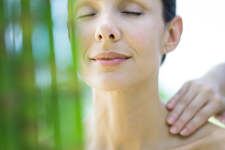 levantandose: Woman having massage, smiling, bamboo in blurred foreground LANG_EVOIMAGES
