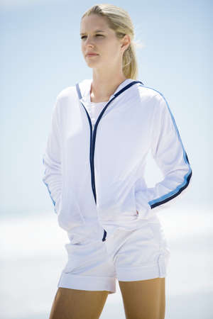 Young woman in active wear, standing on beach