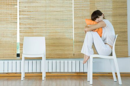 Young woman sitting in chair, hugging cushion LANG_EVOIMAGES