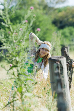 Young woman leaning against rural fence, smiling at camera LANG_EVOIMAGES