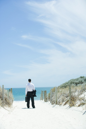 Businessman standing on sandy path leading to ocean, rear view