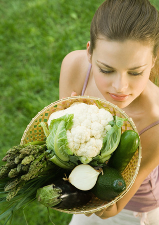 Young woman holding up basket full of vegetables LANG_EVOIMAGES