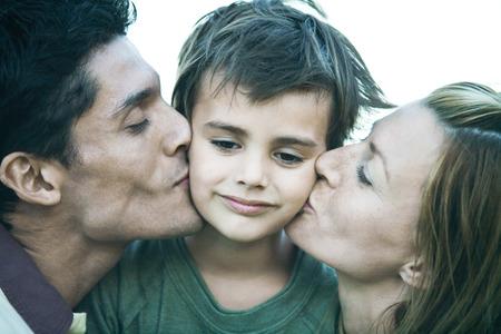 smooching: Man and woman kissing son on cheeks, close-up