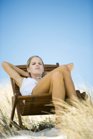 Young woman sitting in deck chair, in dunes