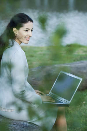 Woman using laptop in park, lake in background LANG_EVOIMAGES