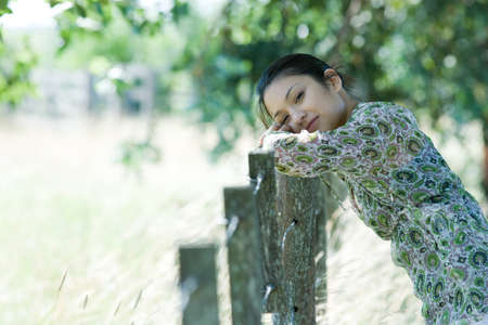 Young woman leaning against rural fence, head resting on arms, smiling at camera