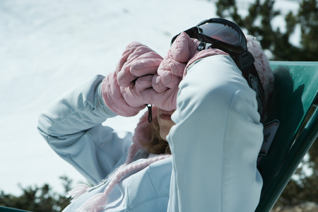 Teen girls sitting in chair in snowy landscape, rubbing eyes with backs of gloved hands