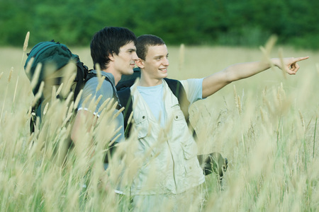 Two hikers standing in field, one pointing out of frame