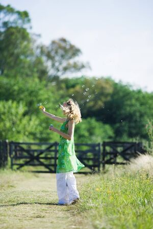 Woman blowing bubbles on rural path, side view