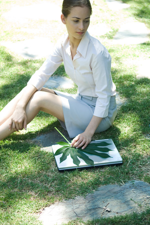 beauties: Woman sitting on grass, holding leaf on top of laptop