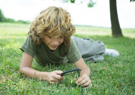 Boy lying in grass with magnifying glass