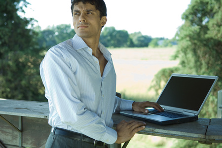 distractions: Businessman standing outdoors, with laptop