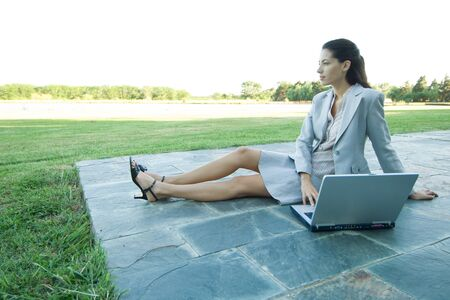 distractions: Businesswoman sitting on patio with laptop, looking away