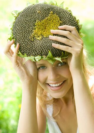 holistic view: Young woman holding up dried sunflower over head LANG_EVOIMAGES