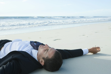 burned out: Businessman lying on sand, at beach