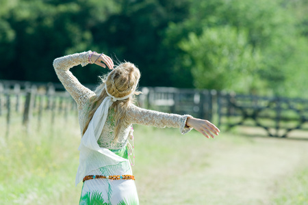 scarves: Young woman standing in field with arm up, rear view