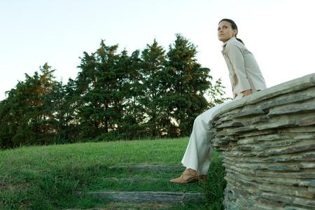 Businesswoman sitting on stone wall