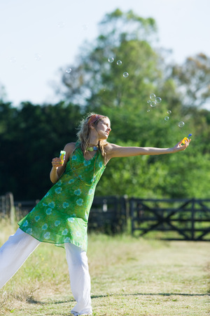 beauties: Young woman blowing bubbles in rural field with arm outstretched, standing on one leg