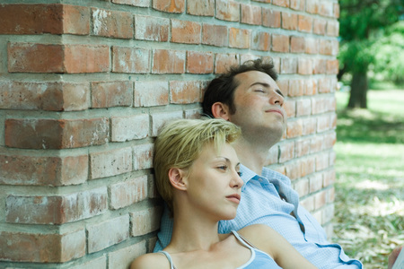 Couple sitting outdoors, leaning against brick wall LANG_EVOIMAGES