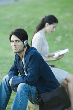 People sitting in park, man listening to headphones while woman reads book LANG_EVOIMAGES